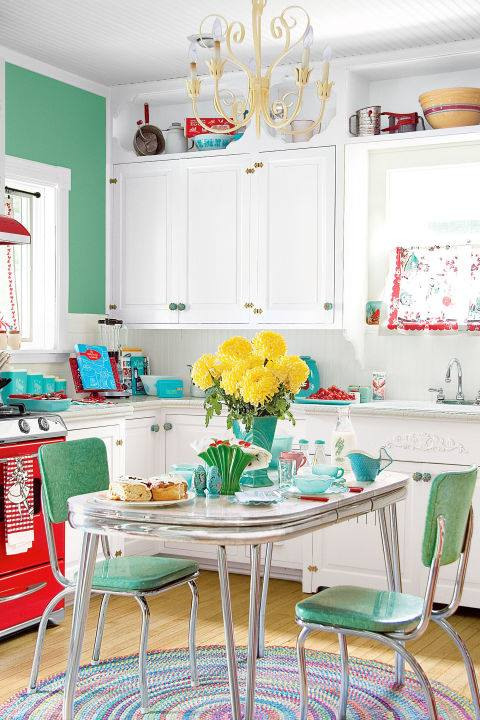 Country Living Retro Style Kitchen With White Cabinetry, Green Chairs, Colorful Accessories & Chandelier